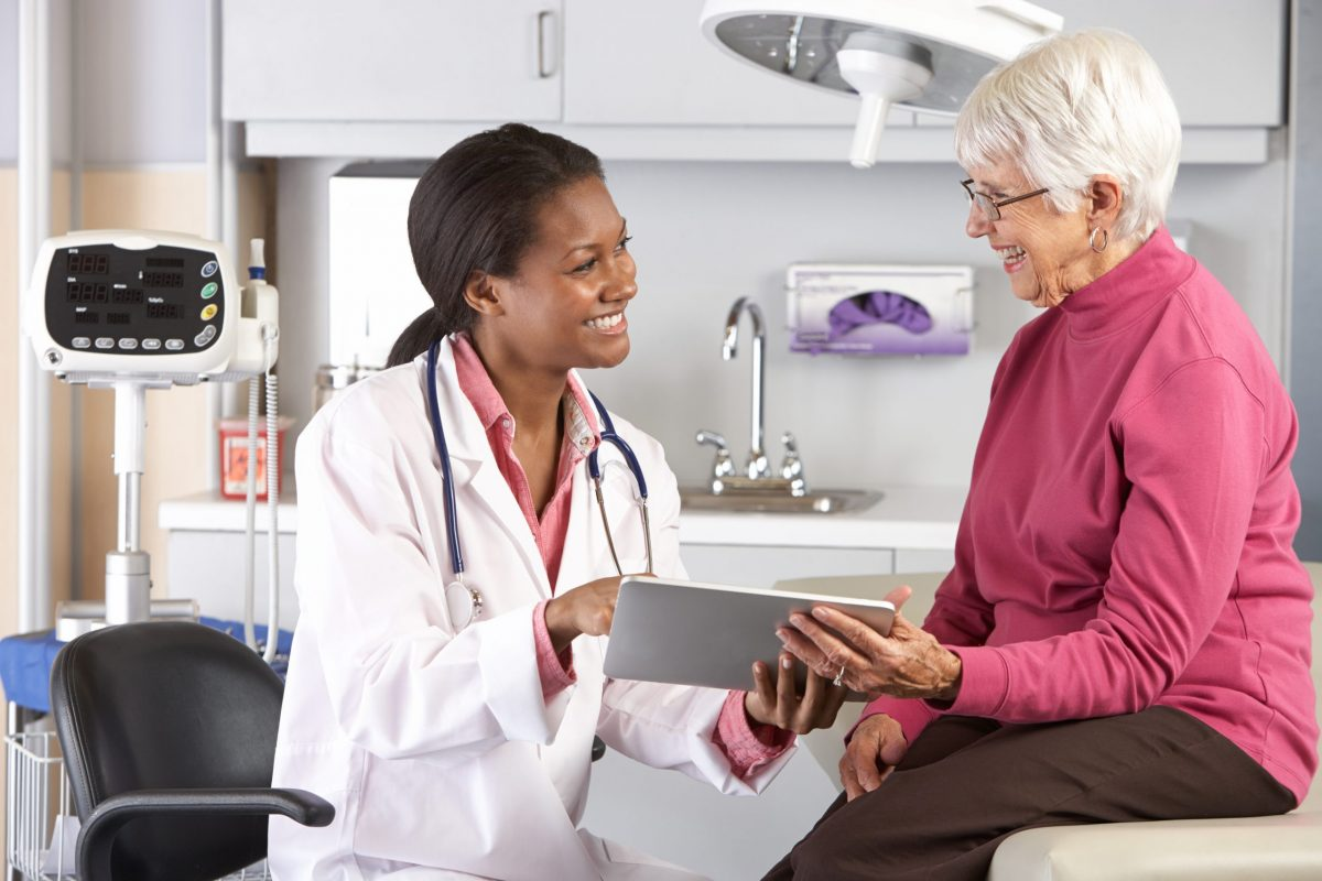 An older woman seeks help from an orthopedic knee specialist to address her pain in a medical office.