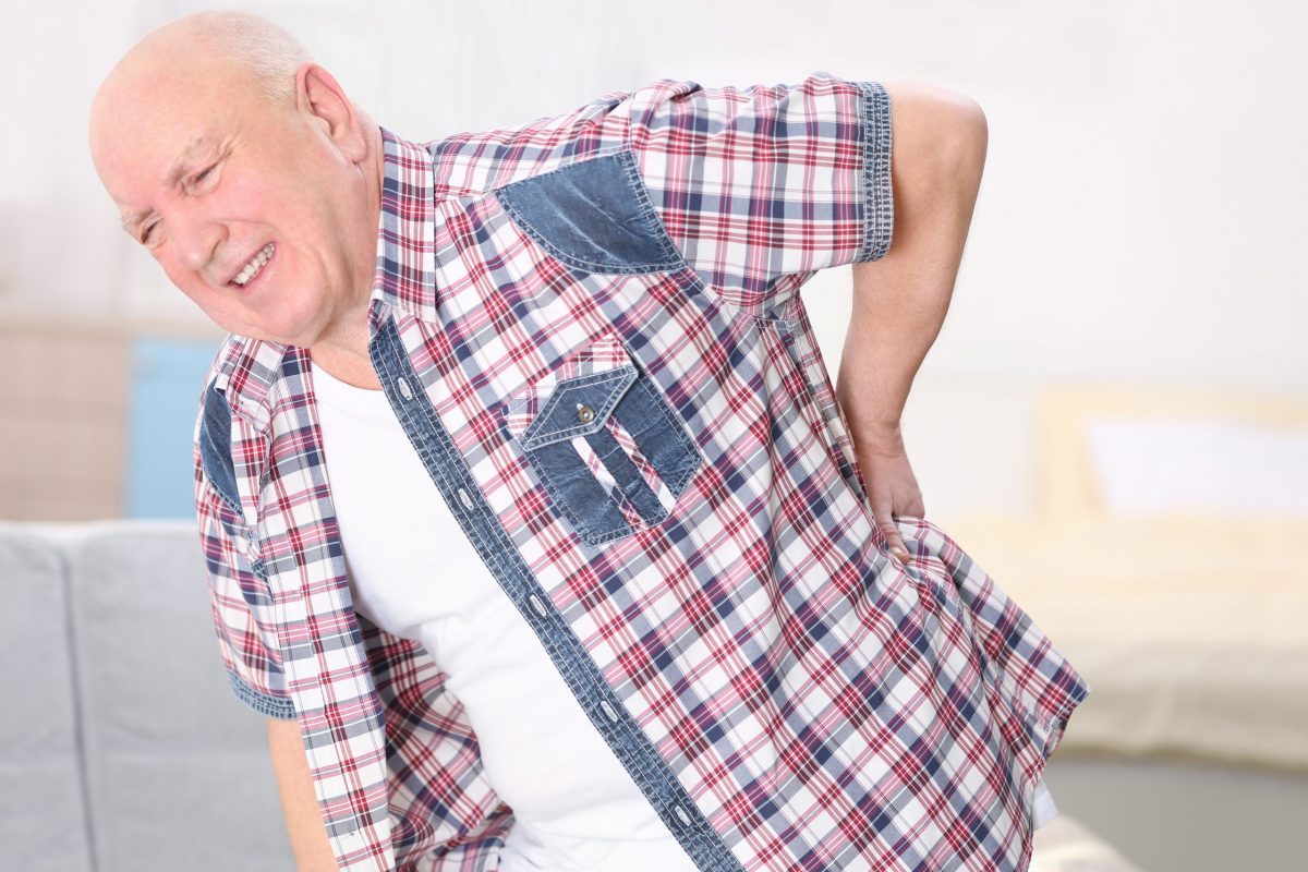 An elderly gentleman in a checkered shirt bends to the side in pain from a herniated disc.