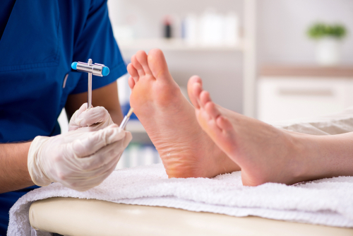A foot and ankle expert is examining a patient for a forefoot deformity, using a medical tool.