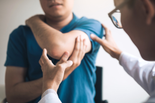 A male orthopedic doctor wearing glasses examines an elbow injury of a male patient wearing a blue shirt.