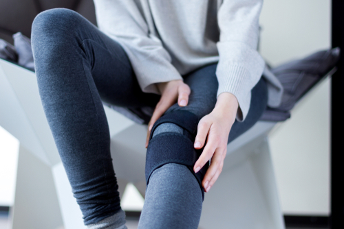 Young woman in gray sweatshirt and leggings holds her braced knee recovering from torn meniscus surgery.