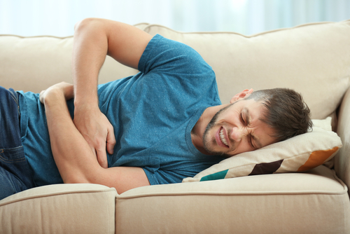 A young man with brown hair wearing a teal t-shirt lays down on a beige couch holding his abdomen in pain.