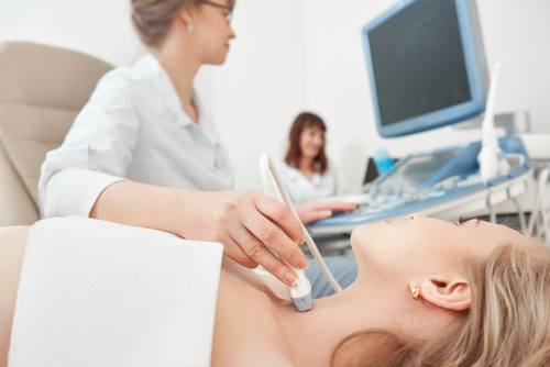 A female orthopedic doctor performs a scan of a blonde female patient's neck to check for thyroid issues.