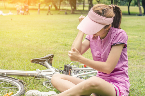 Young woman in a pink polo and pink visor sits on the grass holding her elbow in pain next to her bike.