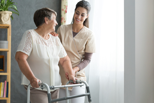 Happy mature woman with a walker being assisted by a smiling nurse after a hip replacement.
