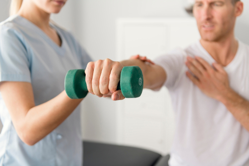 Female physical therapist assists male patient recovering from a rotator cuff injury with weighted shoulder exercise.