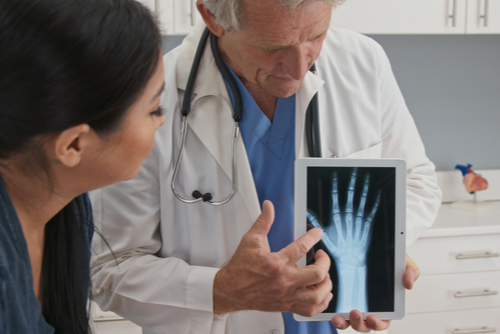 A dark-haired woman patient observes an iPad image of her injured hand; a Doctor points out areas of the hand in need of repair.