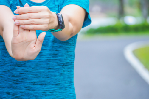 A female athlete in a blue shirt practices a wrist extensor stretch.