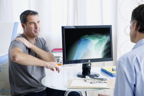 A middle-aged man holds his shoulder in pain while an orthopedic shoulder specialist examines a shoulder X-Ray on a desktop computer.
