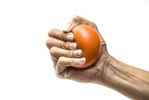 A hand squeezes a foam ball to help improve carpal tunnel syndrome.