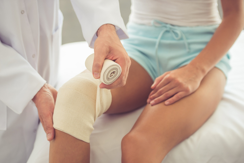 An orthopedic physician helps to secure a broken kneecap with an ace bandage.