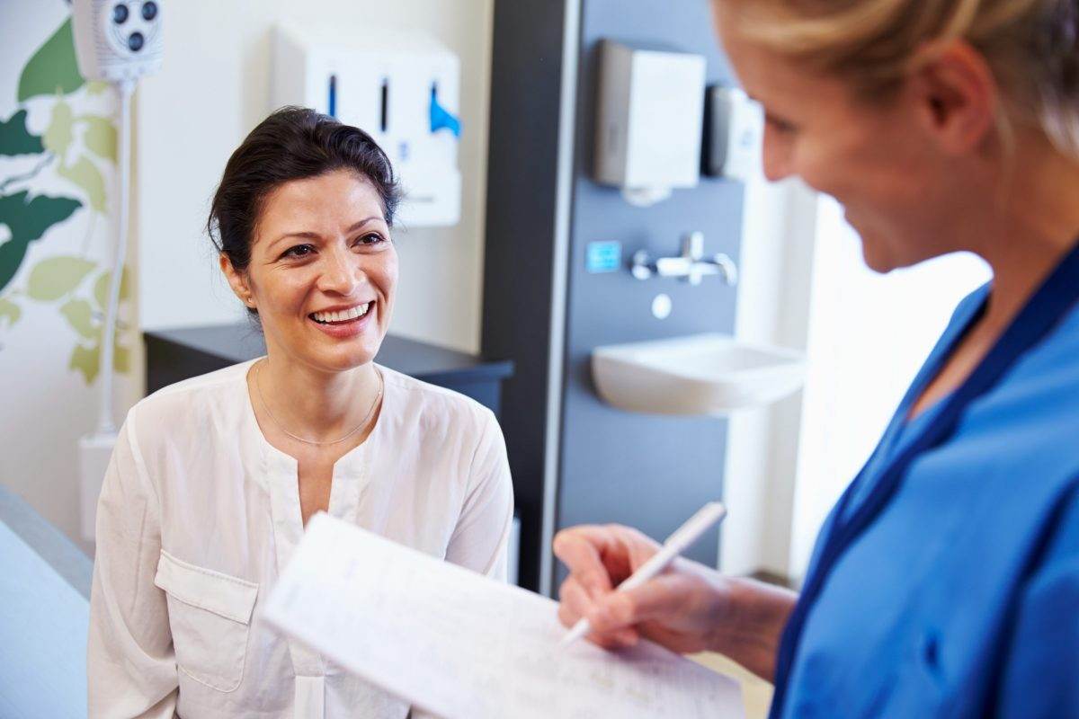 Female doctor talking to her patient as they both smile at each other.