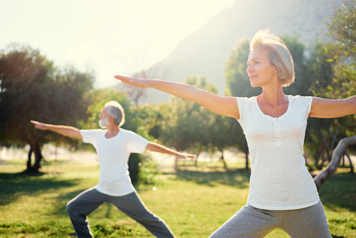 An active middle-aged man and woman are in Warrior B yoga pose on a sunny day in the park.