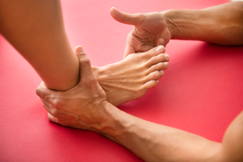A male orthopedic foot and ankle doctor assesses a patient's foot with hallux rigidus for possible big toe replacement.
