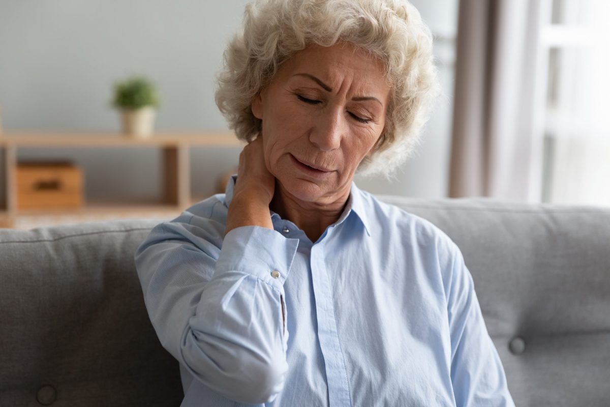 Mature woman wearing a light-blue, button-down shirt rubs her neck in pain sitting on her gray couch at home.