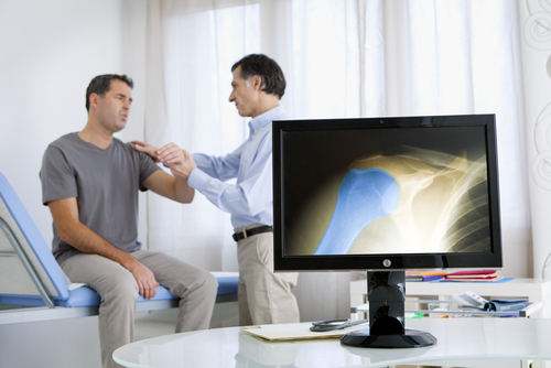 A computer screen highlights an arthritic shoulder, while a doctor examines the stiff, painful shoulder of the male patient.