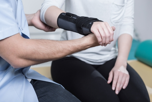 A male occupational therapist assesses the elbow, hand, and wrist of a female patient wearing an arm brace.