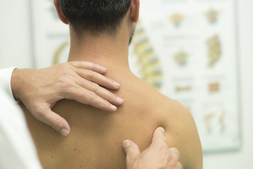 An orthopedic doctor evaluates the shoulder of a male patient with brown hair to help him find frozen shoulder relief.