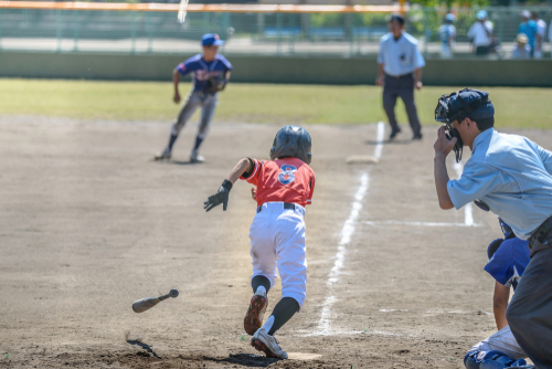 Boy in red baseball uniform drops bat and runs to first base while a boy in a blue baseball uniform guards the base.