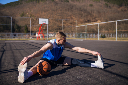 A male with blonde hair wearing a blue shirt performs a seated warm-up stretch on the basketball court next to his basketball.