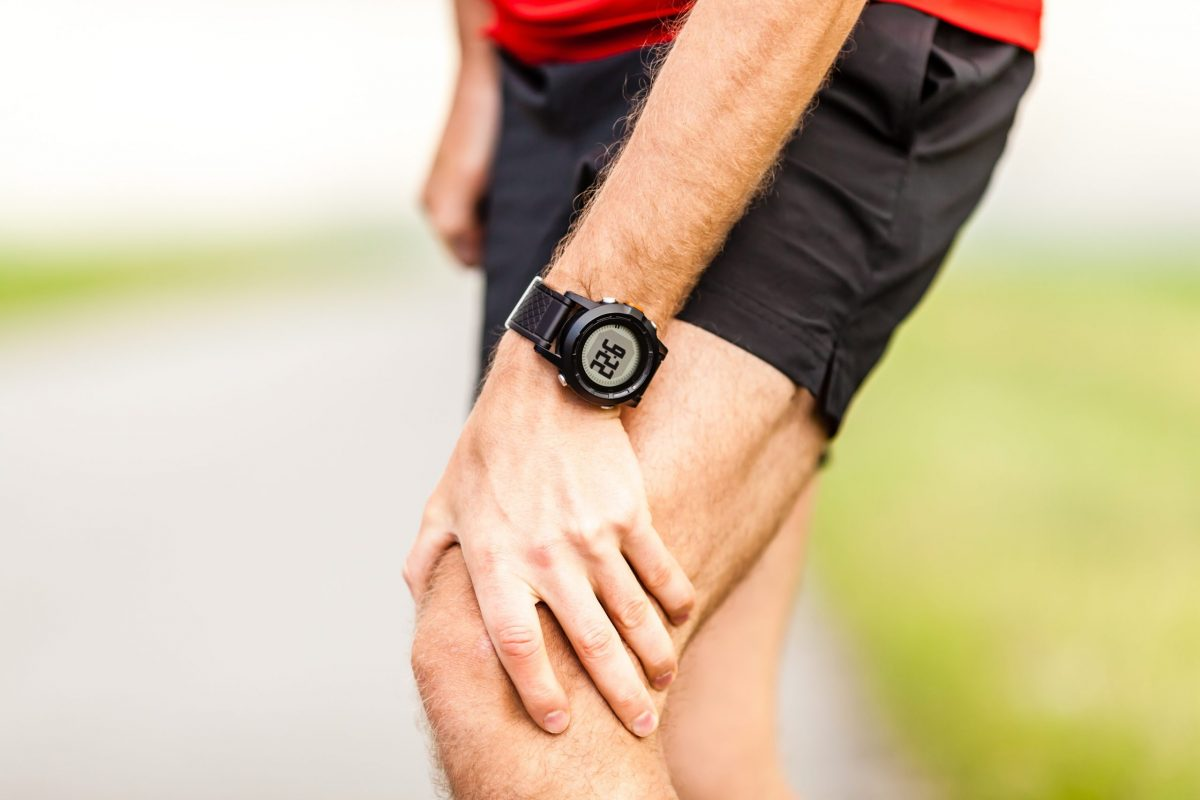 A male runner in black running shorts and wearing black watch holds quadriceps due to pain above knee cap.