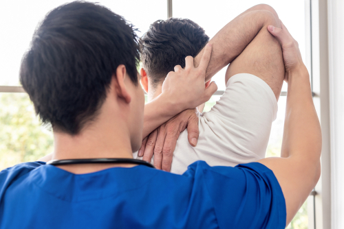Physical therapist stretching upper arm of athlete male patient to relieve tricep muscle pain