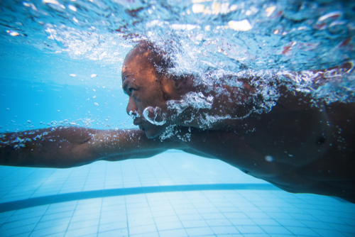 View of man swimming underwater in indoor pool.