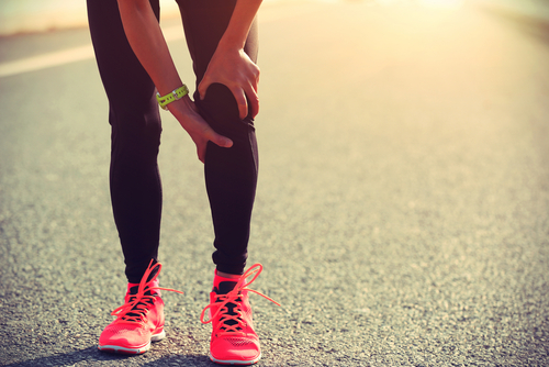 A runner in pink shoes holds her knee in pain, taking a break from running on a blacktop.