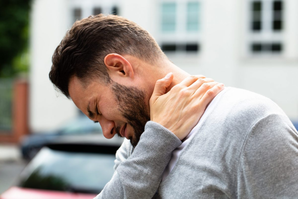 Young bearded man holds his neck because of the pain of a pinched nerve.