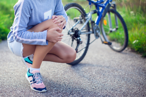A woman in a blue shirt, shorts, and pink shoes squats down to hold her knee in pain, her blue mountain bike in the background.