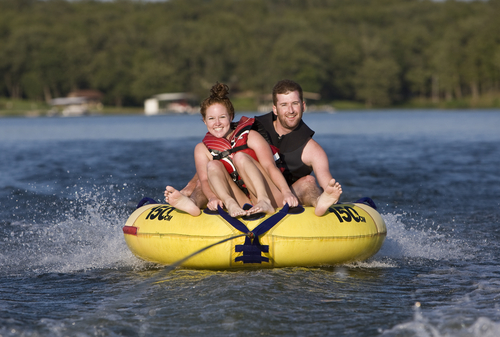 Man and woman in life jackets smiling as they water tube on a lake.