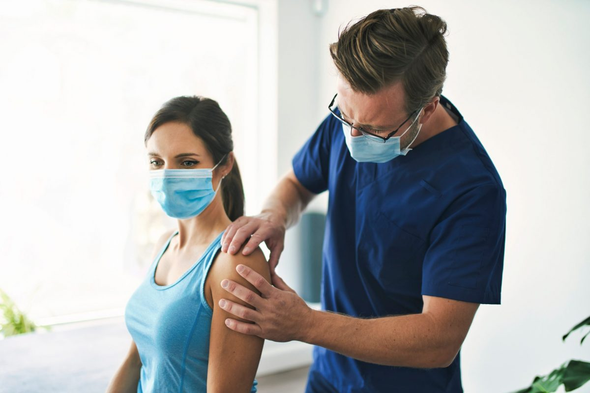 A male orthopedic doctor wearing a mask examines the shoulder of female patient wearing mask, for possible PRP therapy.