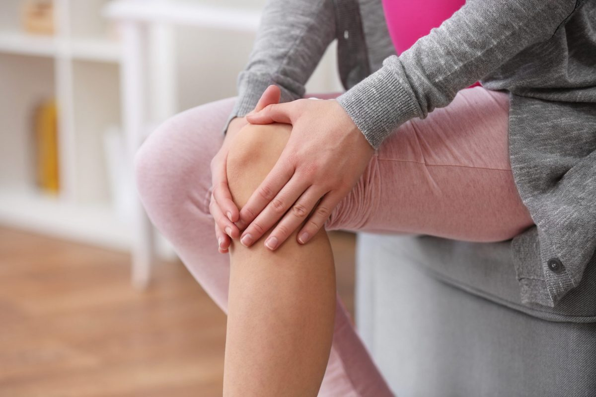 A woman experiences knee pain while sitting at home on her couch.