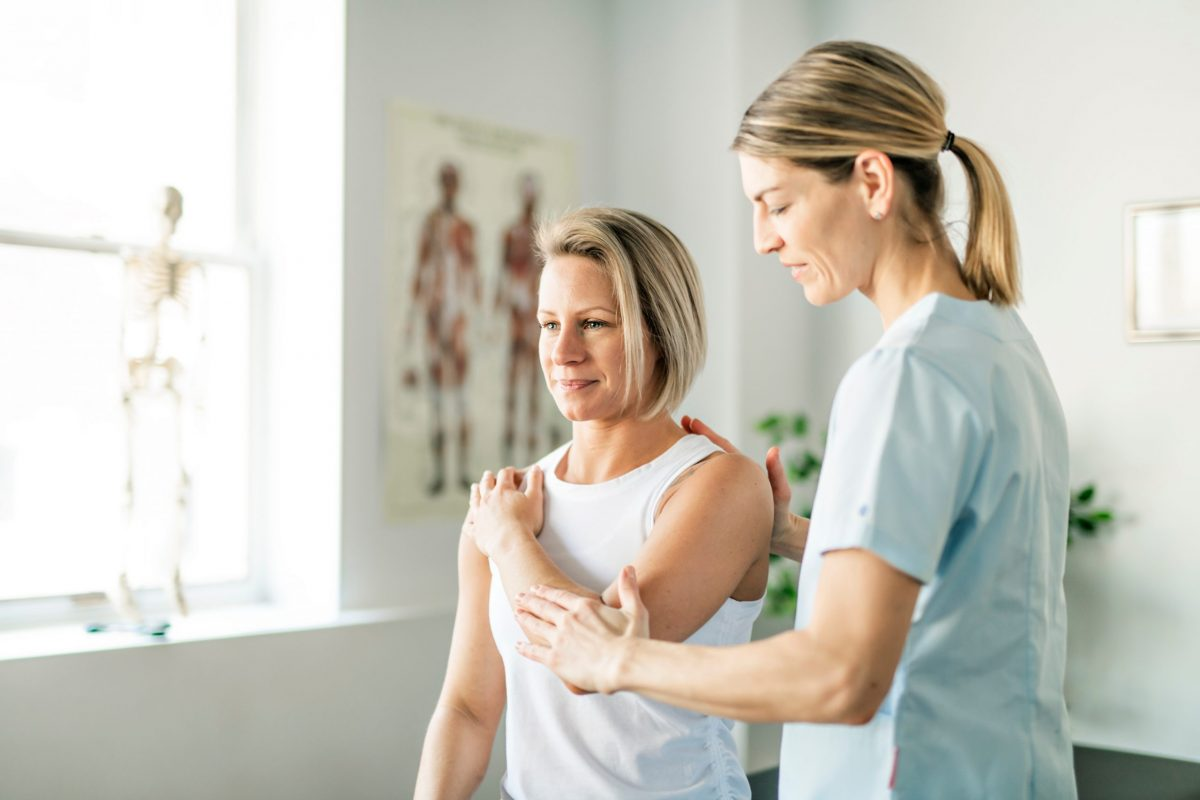 A female orthopedic doctor evaluates a female patient to see if trigger point injections will help her shoulder pain.