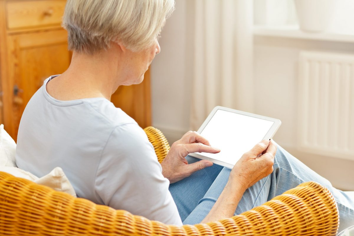 A mature woman with short blonde hair, sitting in a wicker chair, prepares for a telemedicine visit using her tablet.