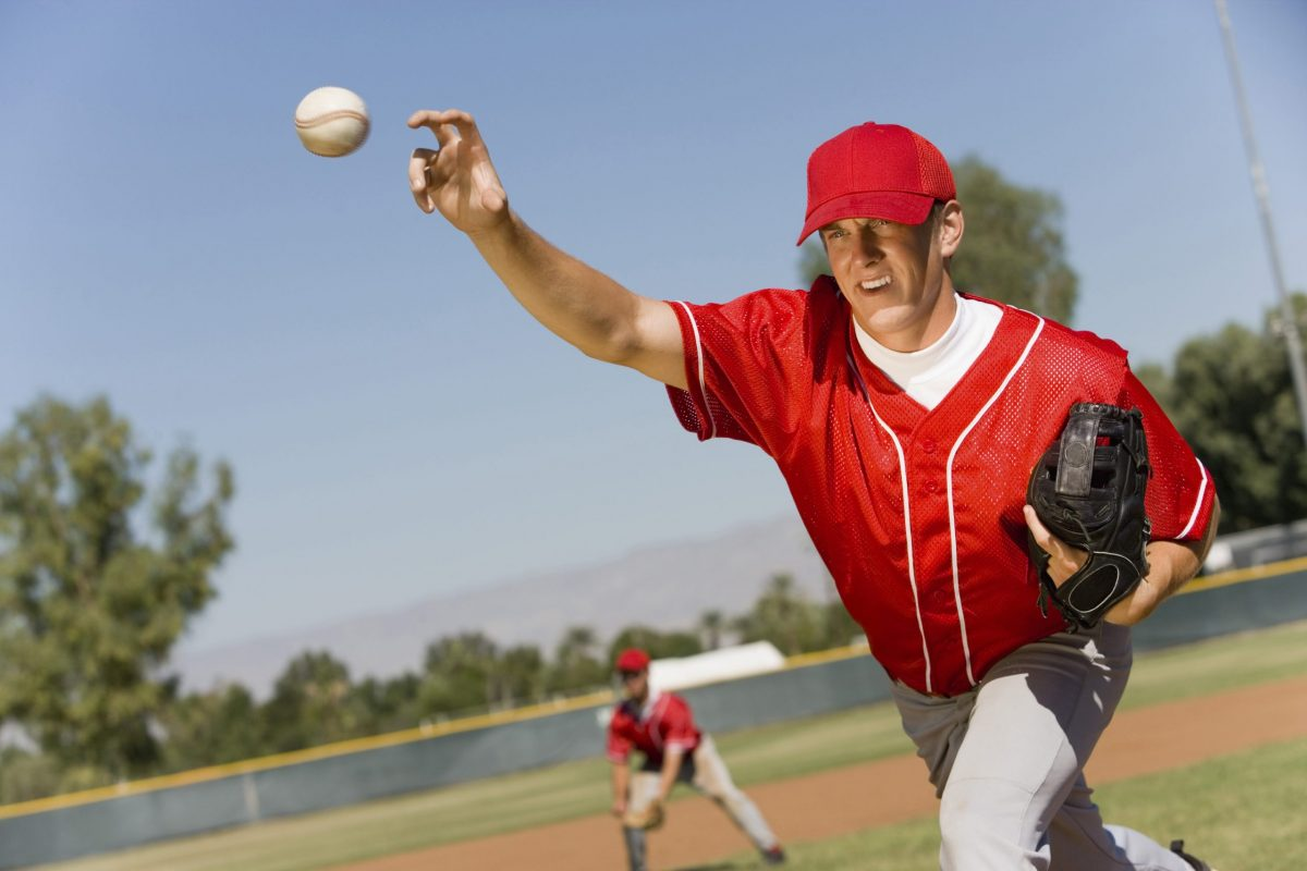 Baseball pitcher in red uniform releases an overhead pitch outside during a baseball game.