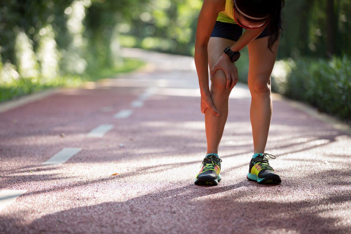 Female runner holds her shin in pain on asphalt running path outside surrounded by greenery.