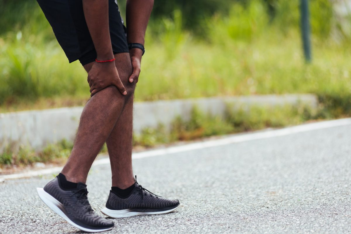 Male person of color holds his knee in pain taking a break from running on pavement surrounded by green grass.