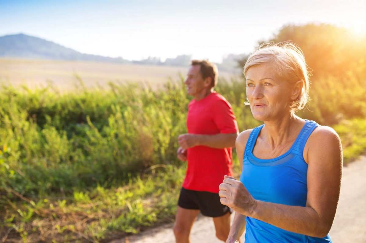 Active seniors running outside on a running path by a green field