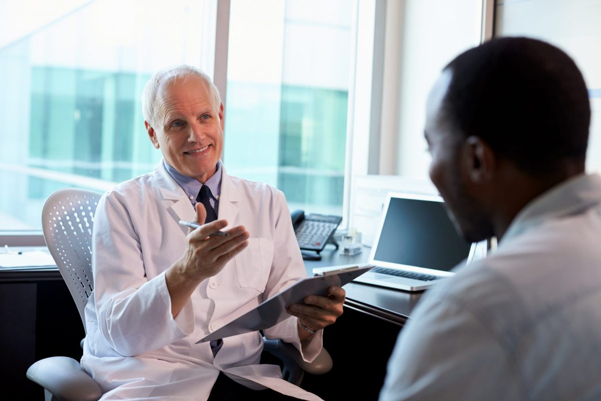 Mature male orthopedic hip surgeon speaks with black man about muscle sparing hip replacement surgery.