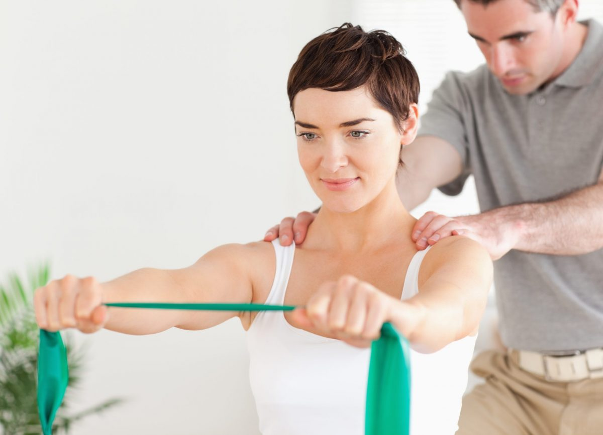 Male physical therapist tests the range of motion on her patient's shoulders.