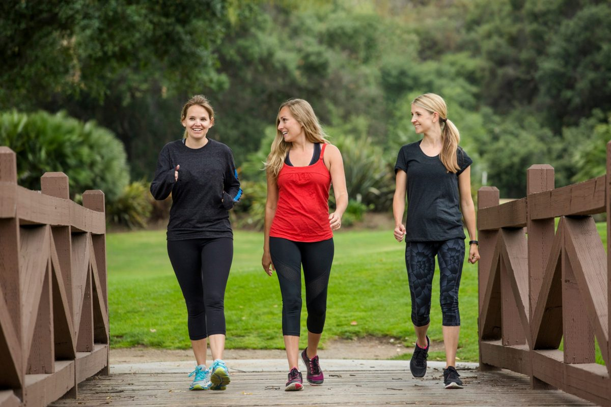 Three women in athletic clothing walk together outside for exercise.